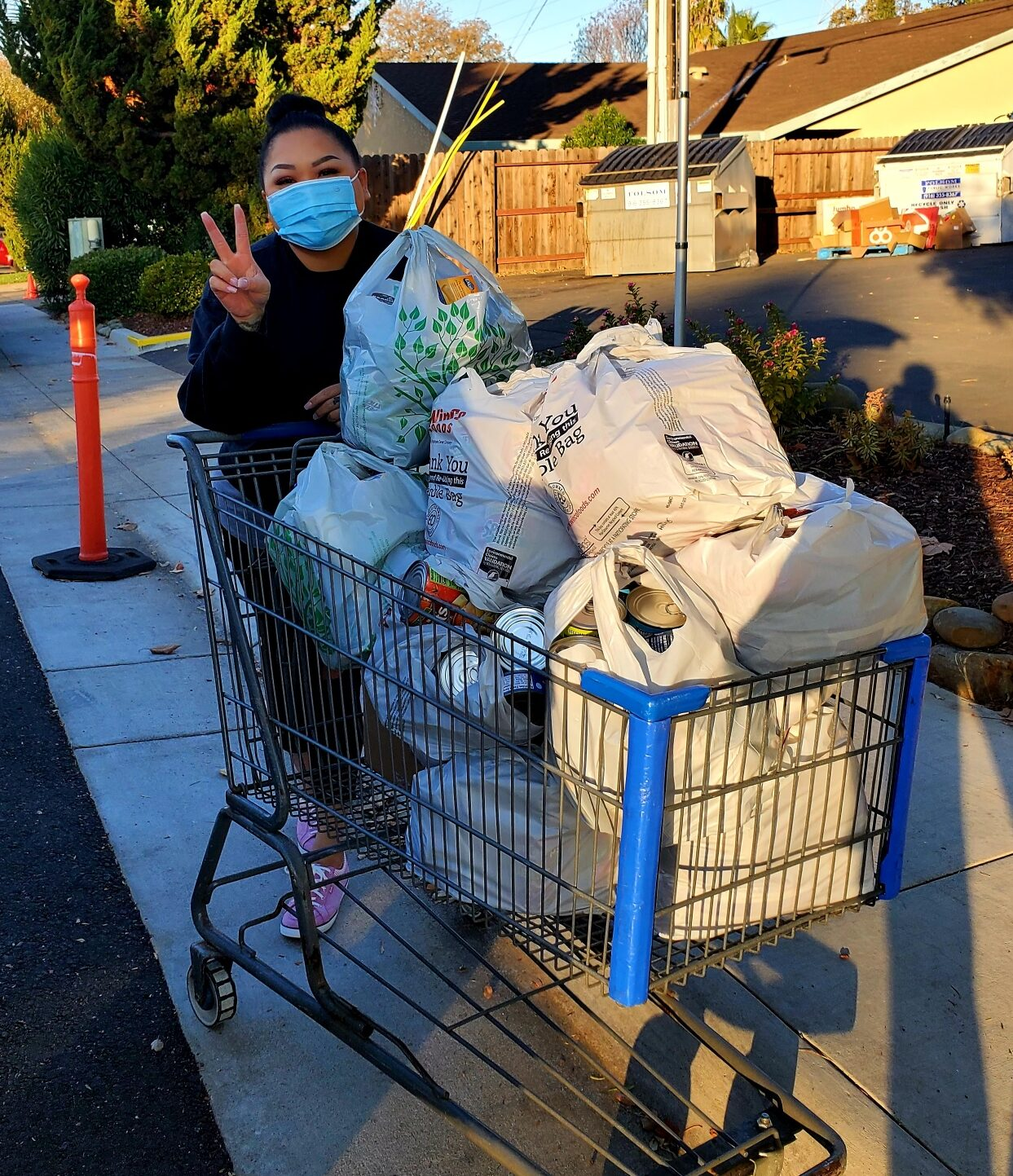 Photo of Yeng Vue donating a shopping cart full of pantry items for the Twin Lakes Food Bank